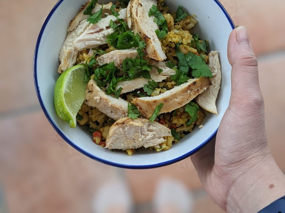 holding Low-FODMAP chicken and rice bowl